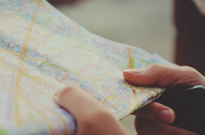 La carte qui est entre les main de la personne représente le référencement web, mais plus spécifiquement le référencement local. L'image représente quelqu'un qui cherche son chemin est c'est très symbolique pour Google map.