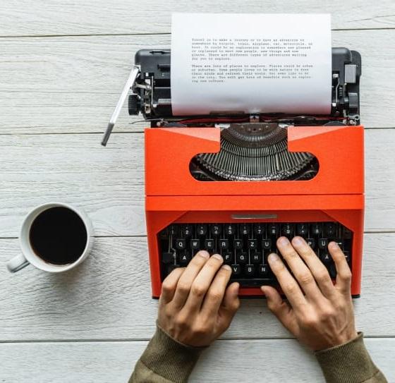 Toute agence de référencement web dépends de la qualité de sa rédacction seo. L'image montre deux mains d'un écrivain qui pianote sur une dactyle orange dont le texte en est à quelques paragraphes. S'il respecte sa densité de mot-clés, il réussira son référencement Internet.